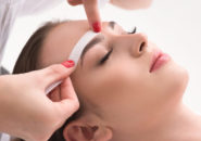 Calm young girl getting eyebrow depilation. Beautician is applying wax paper stick on hair